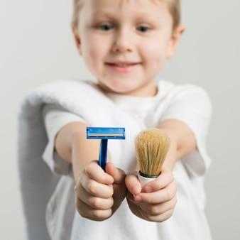 Mise au point sélective d'un garçon souriant montrant le rasoir et le blaireau vers la caméra