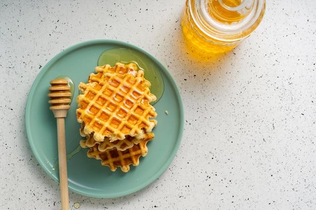 Mise au point sélective, gaufres au sucre belge avec du miel de fleurs sur une plaque bleue