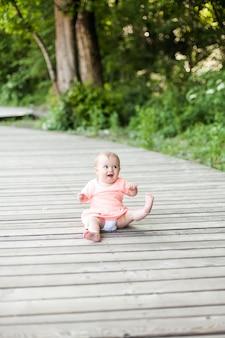 Mise au point sélective de happy 6 mois petit enfant portant une robe rose rampant sur l'herbe et jouant