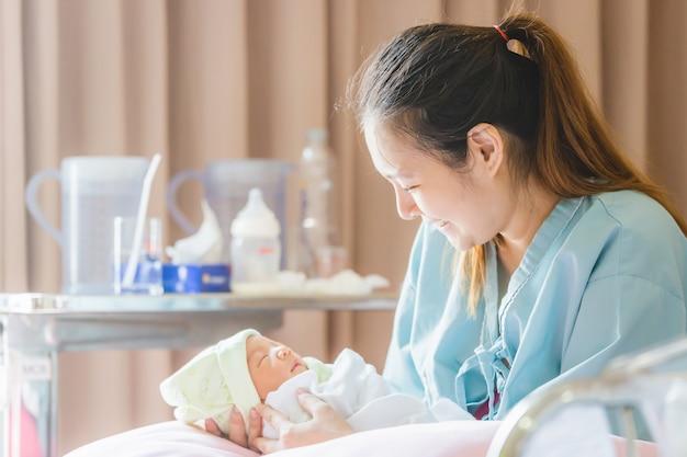 Mise au point sélective de heureuse mère asiatique à la recherche d'un garçon nouveau-né dort dans la main à l'hôpital