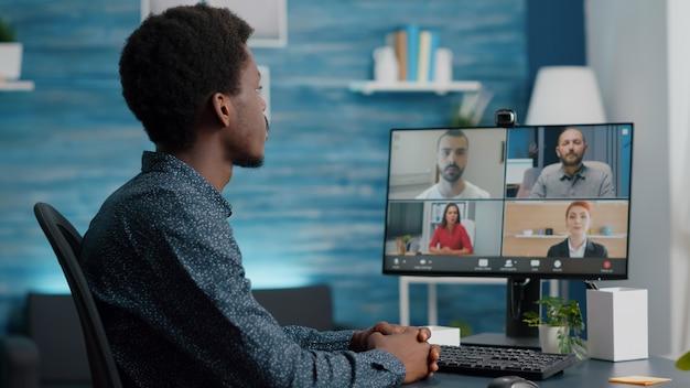 Mise au point sélective sur un homme afro-américain lors d'un appel vidéo de conférence en ligne