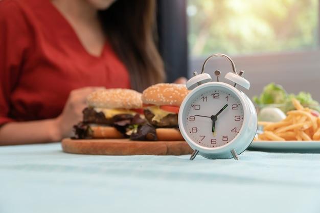 Mise au point sélective de l'horloge, jeune femme prête à manger le petit déjeuner