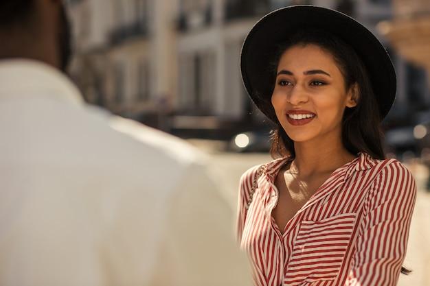 Mise au point sélective d'une jeune femme debout à l'extérieur par beau temps et souriant à un ami devant elle