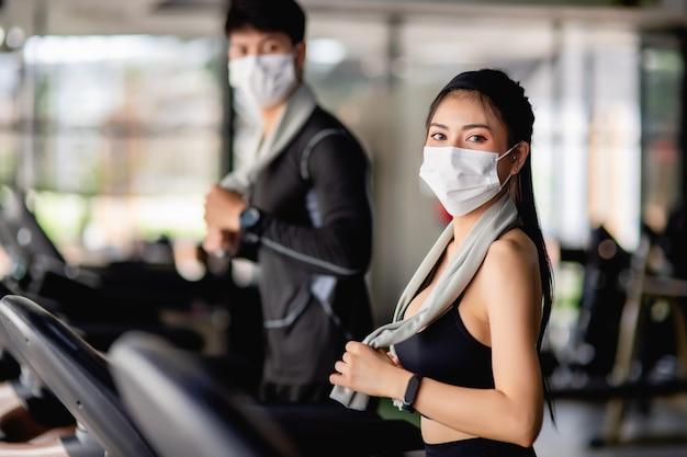 Mise au point sélective, jeune femme sexy en masque portant des vêtements de sport et une montre intelligente et jeune homme flou, ils courent sur un tapis roulant pour s'entraîner dans une salle de sport moderne