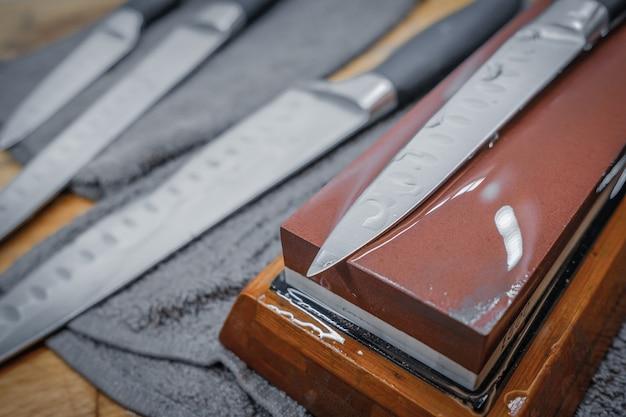 Mise au point sélective sur la lame d'un couteau de cuisine en acier posé sur une pierre à aiguiser à eau