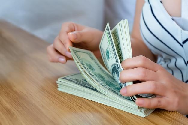 Mise au point sélective d'une main féminine comptant un billet de banque