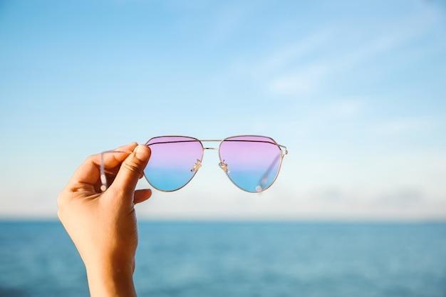Mise au point sélective de la main tenant des lunettes de soleil avec fond océan et ciel bleu