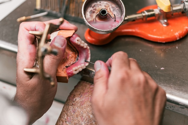 Mise au point sélective sur les mains d'un technicien dentaire fixant la pâte sur une prothèse dentaire dans un atelier