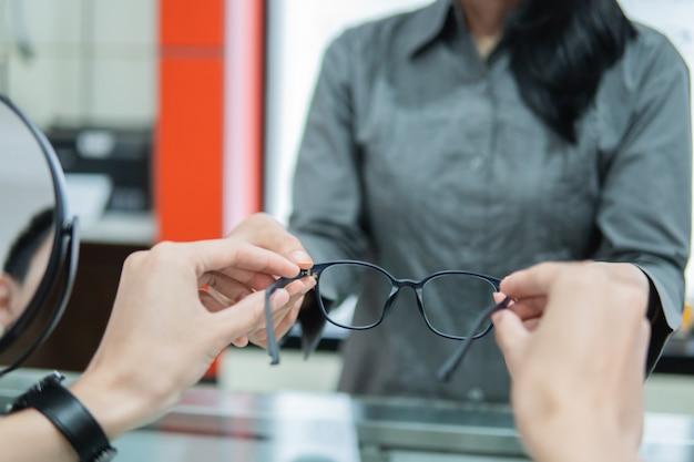 Mise au point sélective des mains d'un vendeur donnant une paire de lunettes aux mains d'un client chez un opticien