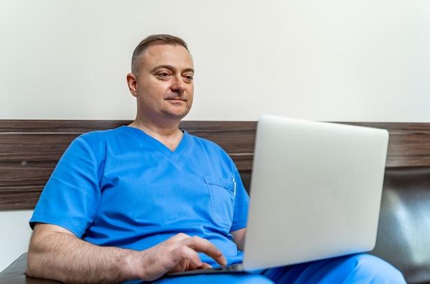 Mise au point sélective sur le médecin en gommages bleus. assis sur un canapé avec un ordinateur portable.