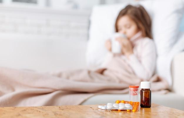 Mise au point sélective des médicaments sur la table tandis que la petite fille malade, boire du thé et couché dans son lit