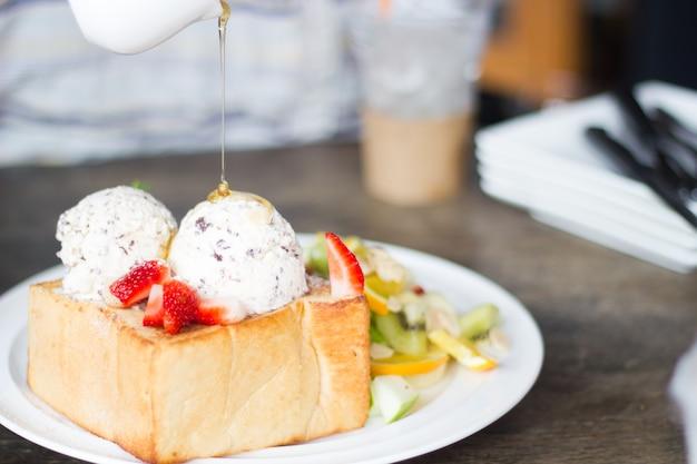 Mise Au Point Sélective De Miel Toast Avec Des Fruits Et De La Glace Sur Un Mauvais éclairage. Photo Premium