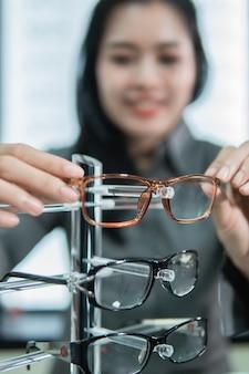 Mise au point sélective des montures de lunettes placées sur une étagère par une cliente après les avoir essayées chez un opticien