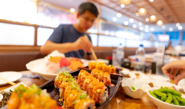 Mise au point sélective de la nourriture japonaise dans un restaurant japonais sushi au saumon avec un homme flou mangeant de la nourriture