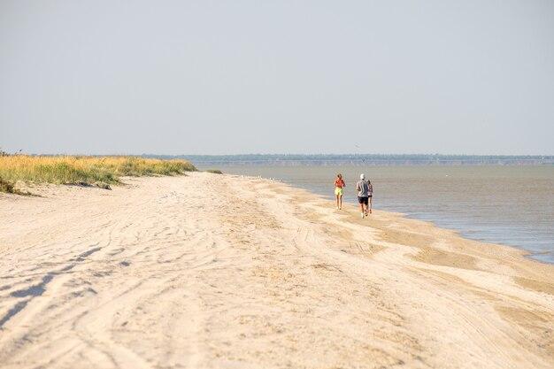 Mise au point sélective par derrière sur un homme qui court le long de la plage le long de la mer