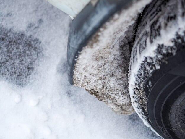 Mise au point sélective le passage de roue de la voiture est obstrué par la glace et la neige