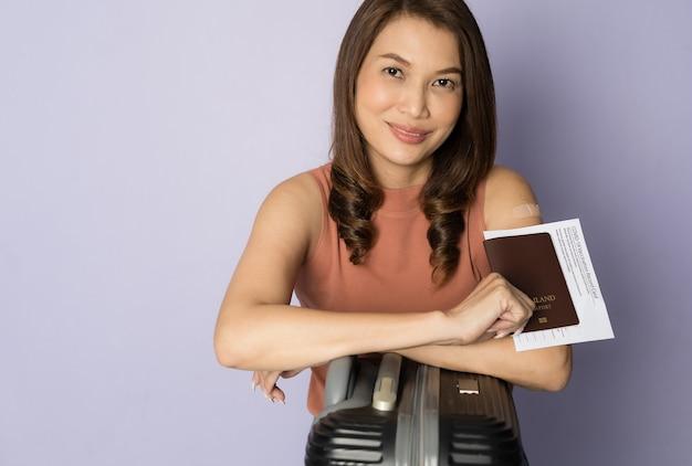 Mise au point sélective sur le passeport, femme asiatique vaccinée tenant un sac de voyage et montrant la carte d'enregistrement d'injection de vaccin et le passeport dans le concept de voyage après la vaccination covid-19 et l'épidémie de virus.