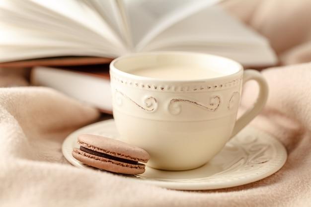 Mise au point sélective photo d'une écharpe tricotée confortable avec une tasse de café et un livre ouvert. style rétro filtré