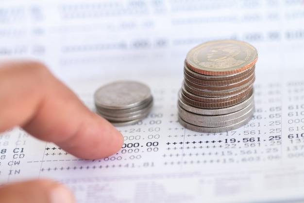 Mise au point sélective des pièces de monnaie thaïlandaises empilées sur la page du relevé de compte bancaire sur fond blanc, collecte d'argent pour le concept d'investissement avec copie espace