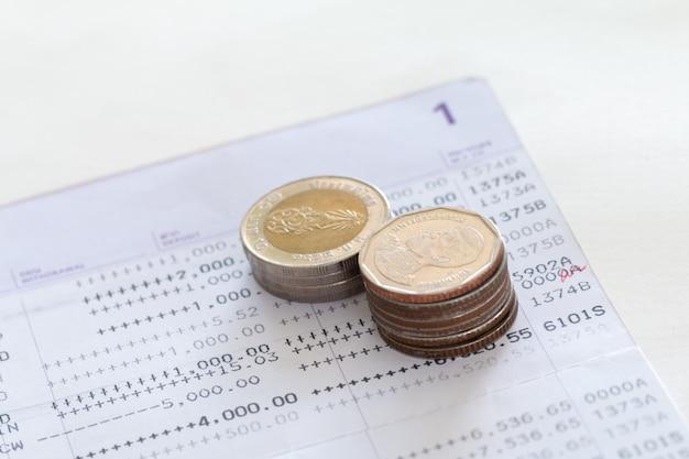 Mise au point sélective des pièces de monnaie thaïlandaises empilées sur la page du relevé de compte bancaire sur fond blanc.