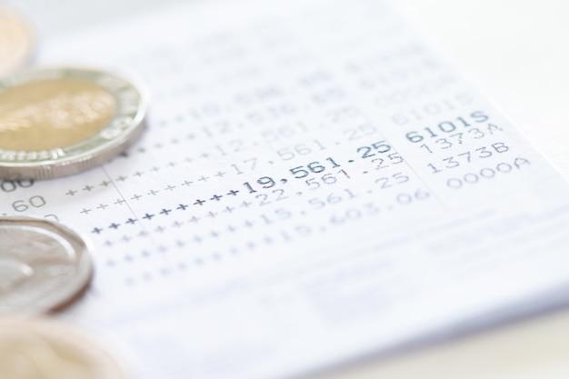 Mise au point sélective des pièces de monnaie thaïlandaises empilées sur la page du relevé de compte bancaire.
