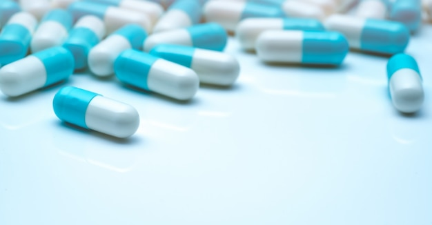 Mise au point sélective sur les pilules à capsule bleu-blanc. capsule pilules sperad sur fond blanc. industrie pharmaceutique. pharmacie.