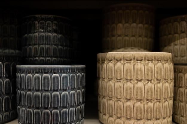 Mise au point sélective sur des pots de fleurs sur une étagère de magasin de jardin. pots en céramique de différentes tailles et couleurs. arrière-plan flou.
