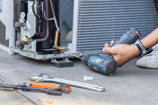Mise au point sélective de la réparation de la climatisation, les mains de l'homme technicien à l'aide d'un tournevis fixant le système de climatisation moderne