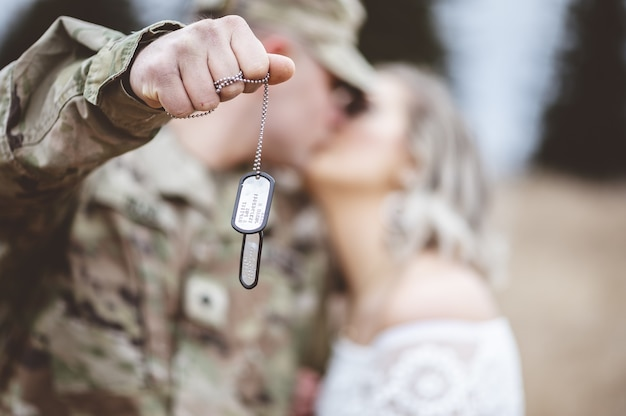 Mise au point sélective d'un soldat américain tenant sa plaque d'identité tout en embrassant sa charmante femme