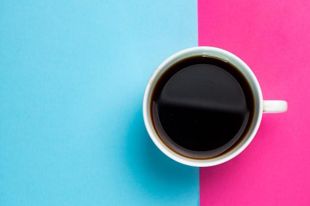 Mise au point sélective, tasse de café blanc sur un double fond de papier, bleu et rose