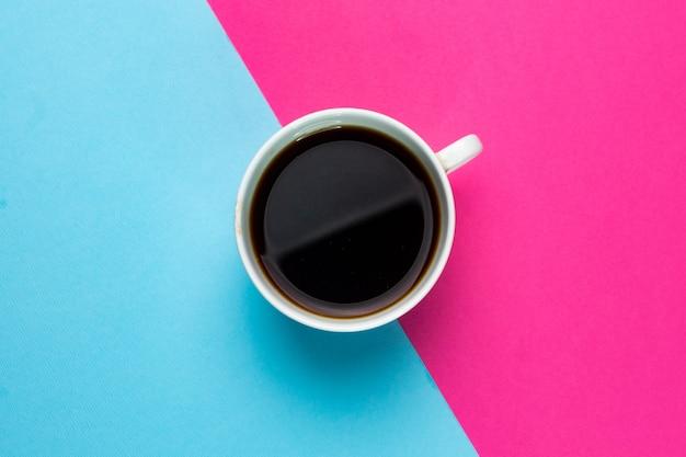 Mise au point sélective, tasse à café blanche sur papier double, bleu et rose