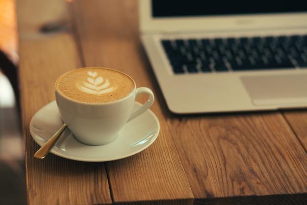 Mise au point sélective d'une tasse de café blanche placée sur une assiette. ordinateur portable moderne sur le fond derrière la tasse