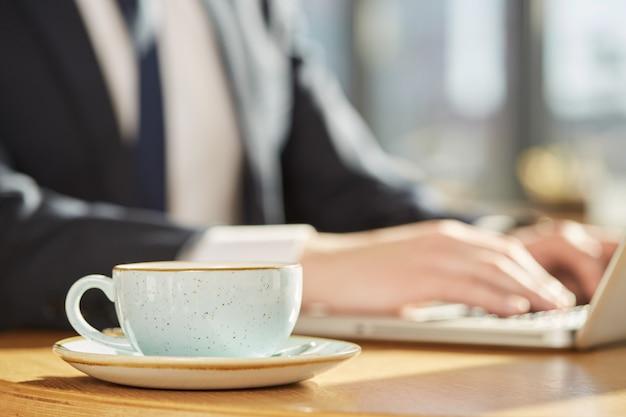 Mise au point sélective sur une tasse de café, homme d'affaires travaillant sur un ordinateur portable sur le fond