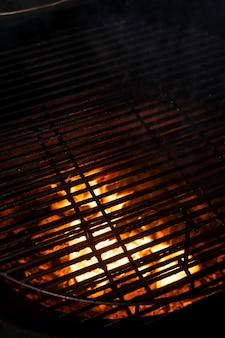 Mise au point sélective, texture du feu, gril avec des charbons ardents. arrière-plan pour les menus et les annonces