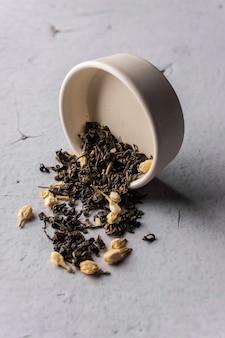 Mise au point sélective, thé noir naturel aux fleurs de jasmin. brasser dans un bol en argile. angle vertical, macro. sur fond clair. pour les menus et les cafés