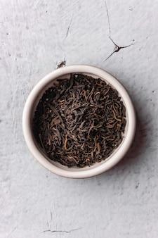 Mise au point sélective, thé noir naturel en feuilles. brasser dans un bol en argile. angle vertical, macro. sur fond clair. pour les menus et les cafés