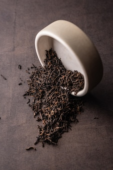 Mise au point sélective, thé noir naturel en feuilles. brasser dans un bol en argile. angle vertical, macro. sur fond sombre. pour les menus et les cafés