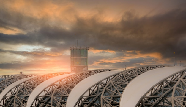 Mise au point sélective sur le toit de l'aéroport et flou de la tour de contrôle du trafic aérien dans l'aéroport contre le ciel sombre