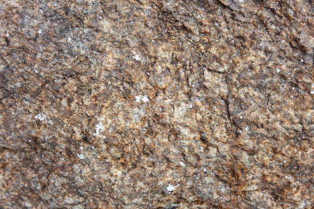 Mise au point sélective de vieilles pierres rustiques et brutes de granit brun