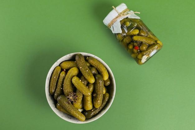 Mise en conserve maison. cornichons de concombres marinés à l'aneth et à l'ail dans un bocal en verre sur fond vert.