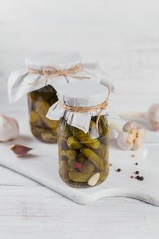 Mise en conserve maison. cornichons de concombres marinés à l'aneth et l'ail dans un bocal en verre sur la table en bois blanc