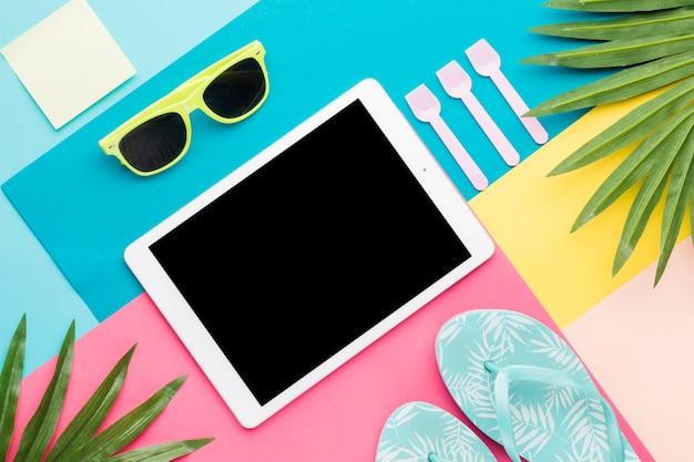 Mise en page créative d'accessoires de plage et tablette