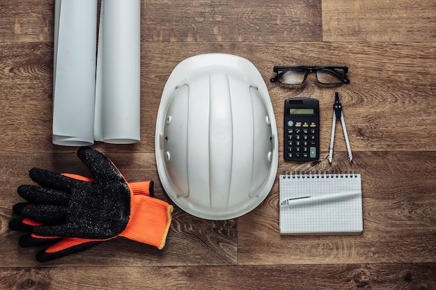 Mise en page créative des architectes avec des dessins au rouleau, des outils d'ingénierie et de la papeterie au sol, espace de travail. vue de dessus. mise à plat.