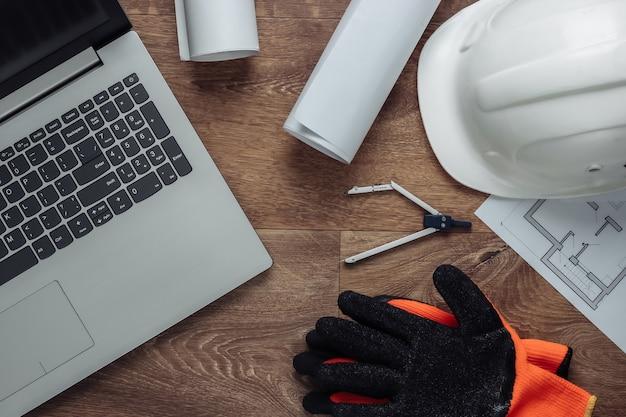 Mise en page créative des architectes avec dessins au rouleau, plan de projet architectural, casque de construction au sol, espace de travail avec ordinateur portable. vue de dessus. mise à plat
