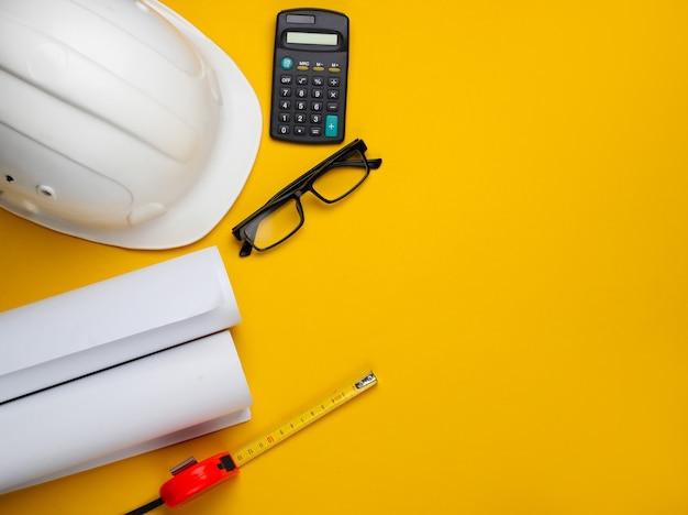 Mise en page créative des architectes avec dessins au rouleau, plan de projet architectural, outils d'ingénierie et papeterie sur fond jaune, espace de travail. vue de dessus. mise à plat. copier l'espace