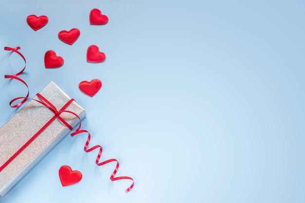 Mise en page créative avec boîte-cadeau et coeurs en tissu rouge sur fond bleu