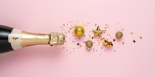 Mise en page créative avec bouteille de champagne et décoration de paillettes d'or.