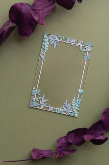 Mise en page créative avec certificat de carte acrylique transparent vierge avec des feuilles vertes sur fond vert écologique