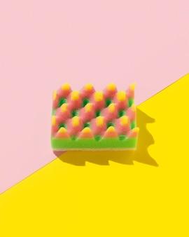 Mise en page créative avec une éponge pour la vaisselle sur fond multicolore. concept de service de nettoyage