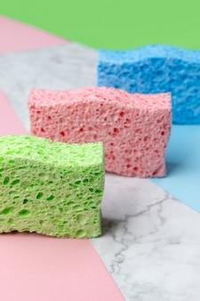 Mise en page créative avec des éponges pour la vaisselle sur fond multicolore. modèle de service de nettoyage